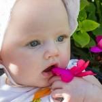 Alicia sitter i parken och luktar på blommorna